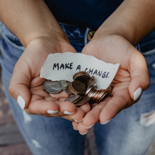 "Hands outstretched holding change. ""Make a change"" is written on a piece of paper and above the change in hands."