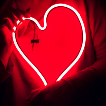 Person holding a neon heart sign