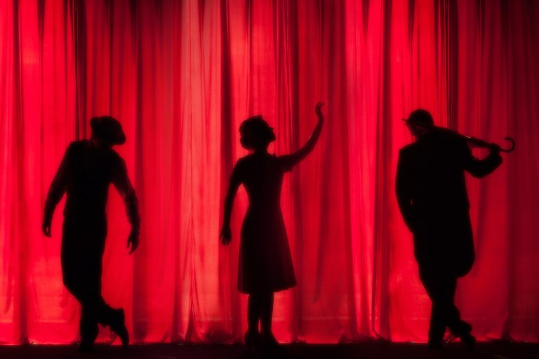 Silhouette of three people against a red curtain
