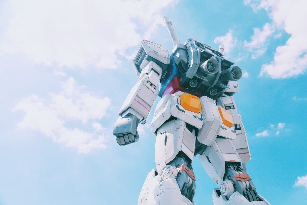 giant Gundam model from behind and below with cloudy sky