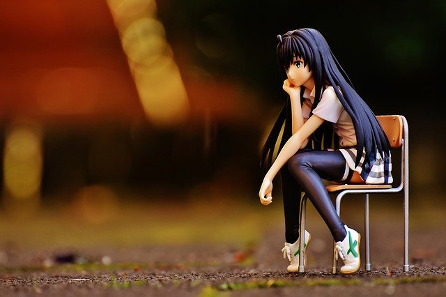 female anime figure sitting in chair thinking